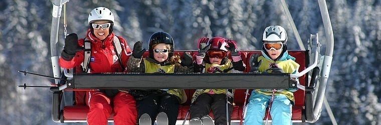 Kinder sitzen im Skilift