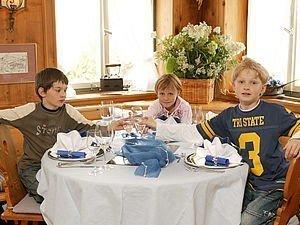 Drei Kinder sitzen am Tisch im Restaurant