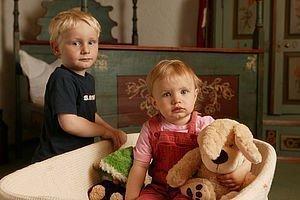 Zwei Kinder mit Kuscheltieren
