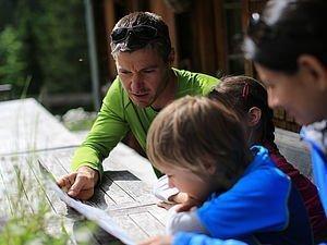 Familie beim Planen der Wanderroute